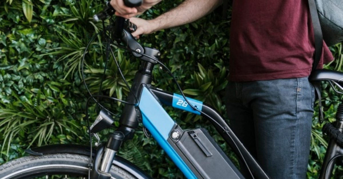 close-up-sideways-cyclist-holding-e-bike-with-green-wall-background_23-2148225875