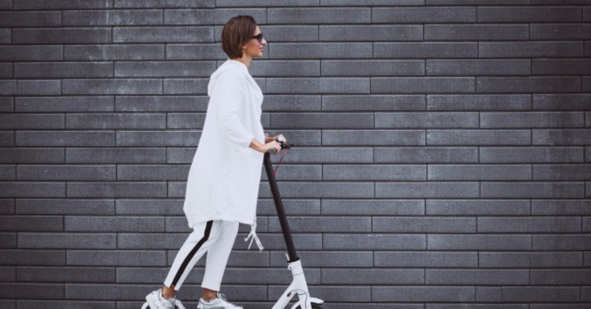 young-woman-dressed-white-riding-scooter_1303-15769