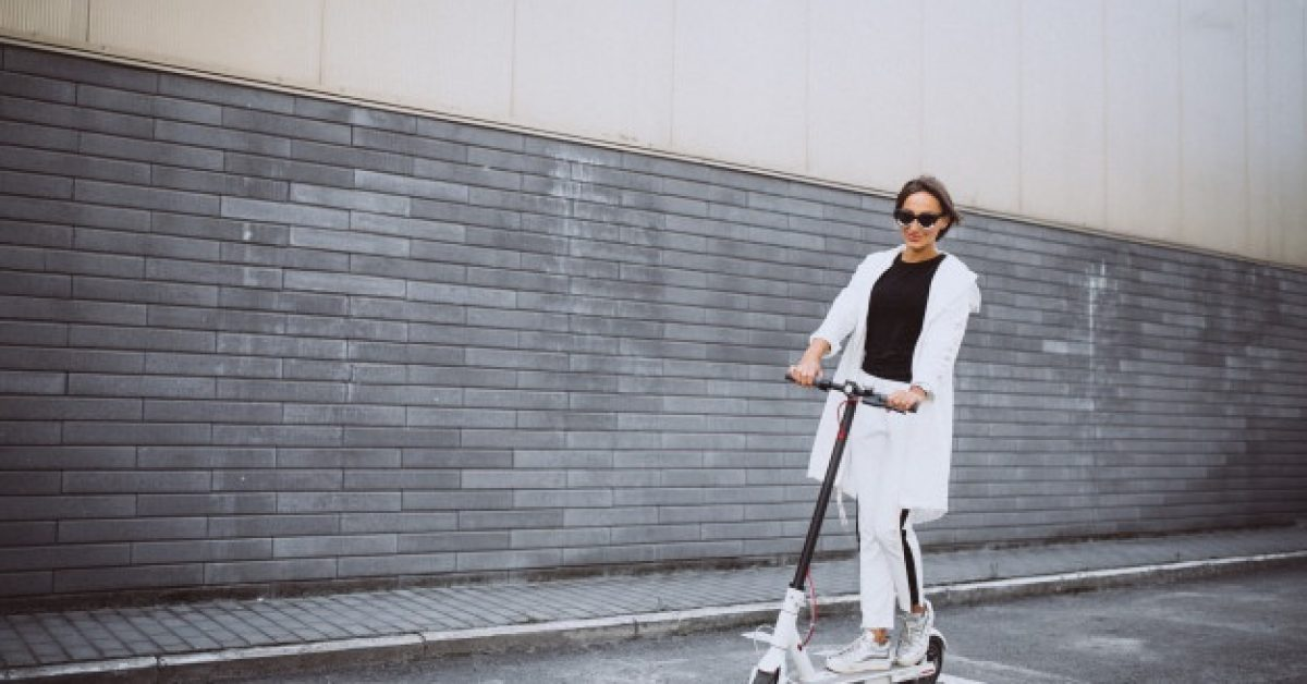 young-woman-dressed-white-riding-scooter_1303-15771