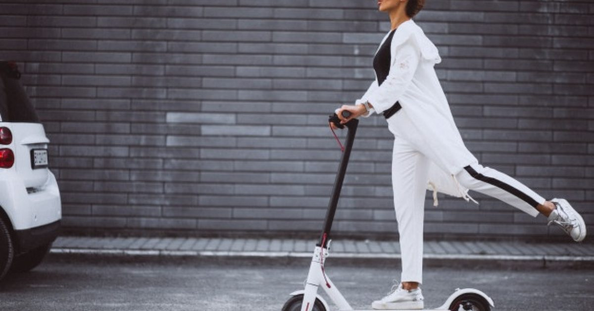 young-woman-dressed-white-riding-scooter_1303-15772