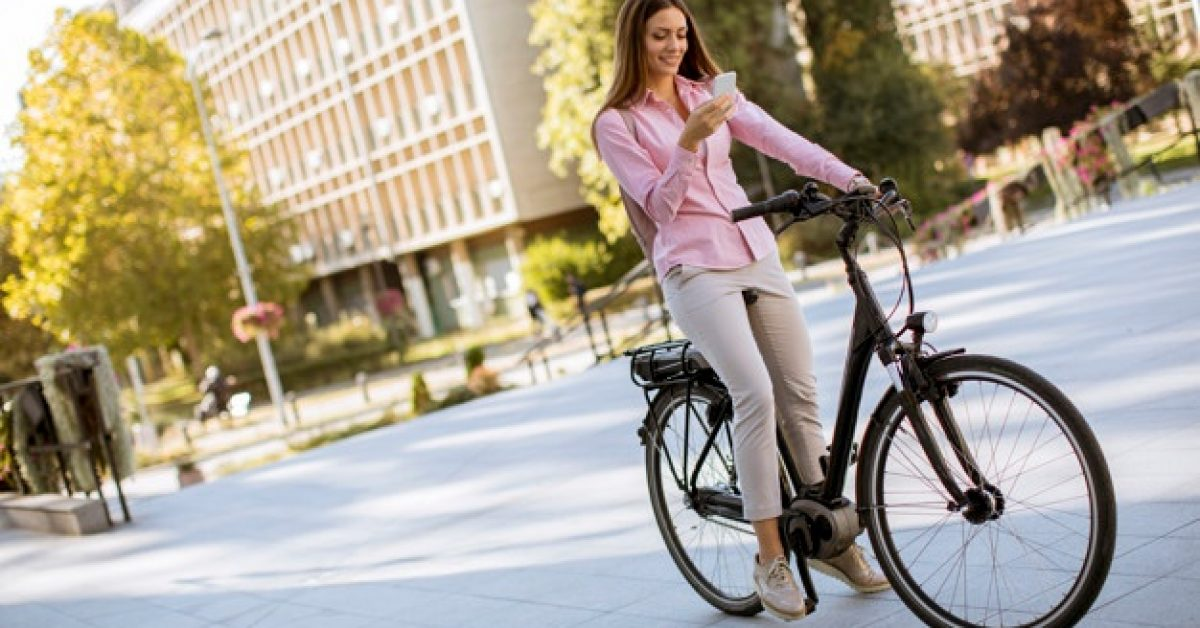 young-woman-riding-electric-bicycle-using-mobile-phone-urban-environment_52137-27812